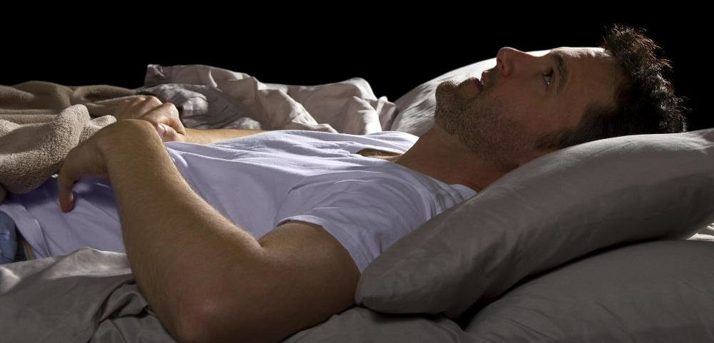 UNILAD UNILAD man in white shirt lying awake in bed3917929306